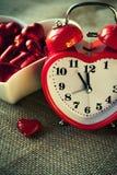 Horloge en forme de coeur rouge avec des chocolats sucrés Images stock