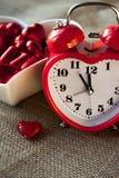 Horloge en forme de coeur rouge avec des chocolats sucrés Photos libres de droits