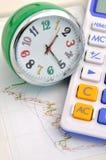 Horloge et calculatrice sur le graphique courant Photographie stock