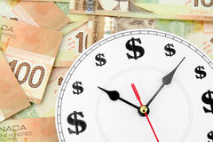 Horloge et dollars canadiens Photo stock