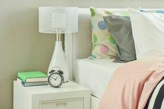 Horloge et lampe de table blanche à côté de literie rayée Photographie stock libre de droits