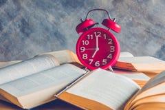 Horloge et livre Photos stock