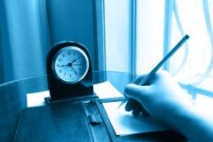 Horloge et main d'écriture sur la note Photographie stock