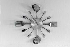Horloge faite de cuillères et fourchettes sur le mur Photo stock