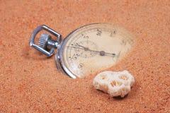 Horloge in het zand met zeeschelp. Stock Afbeelding
