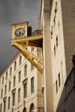 Horloge impressionnante d'or du côté d'un bâtiment Photographie stock