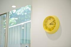 Horloge jaune sur le mur photographie stock
