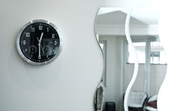 Horloge murale et miroirs noirs ronds Photographie stock