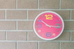 Horloge murale rose de plan rapproché sur le fond texturisé de mur de briques Images stock