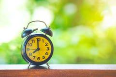 Horloge noire de bureau avec l'écran jaune sur le Tableau en bois Photo stock