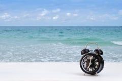 Horloge noire sur le fond blanc de mer de table et de tache floue Photographie stock