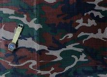 Horloge op camouflage netto achtergrond Royalty-vrije Stock Foto