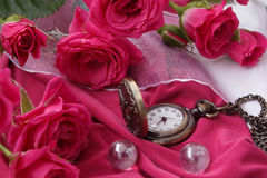 Horloge op een ketting onder de rozen Stock Fotografie