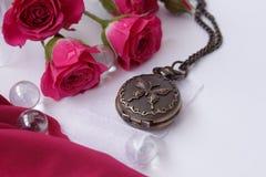 Horloge op een ketting onder de rozen Royalty-vrije Stock Afbeeldingen