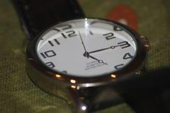 Horloge op greenbackground stock afbeeldingen