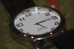 Horloge op greenbackground stock fotografie