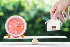 Horloge orange et main d'équilibre tenant la petite résidence sur en bois photo libre de droits