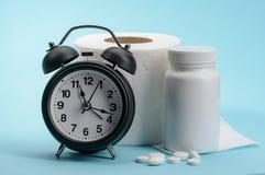 Horloge, papier hygi?nique et pilules photographie stock