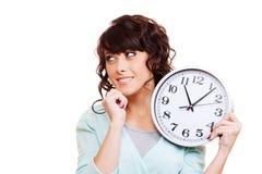 Horloge pensive de fixation de jeune femme Image stock