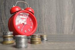 Horloge rouge de style ancien avec une certaine somme d'argent autour Photographie stock