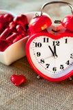 Horloge rouge en forme de coeur d'amour de Valentine avec des chocolats sucrés Images stock