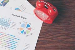 Horloge rouge sur le diagramme sur le fond en bois Fond d'affaires, finances, impôt, rendant compte Temps de concept de se réveil Photo stock