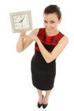 Horloge se tenante gaie de femme d'affaires d'isolement sur le blanc Image stock