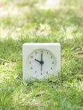 Horloge simple blanche sur la cour de pelouse, horloge de ` du 10h00 dix o Image stock