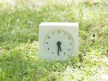 Horloge simple blanche sur la cour de pelouse, 5h30 cinq trente demi Images stock