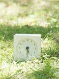 Horloge simple blanche sur la cour de pelouse, 5h30 cinq trente demi Photos stock