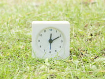 Horloge simple blanche sur la cour de pelouse, 12h10 douze dix Photographie stock