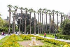 Horloge solaire et touristes détendant dans le jardin national d'Athènes image libre de droits