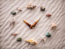Horloge stylisée de cadran pour des coquilles sur le sable pour la concentration et la relaxation pour l'harmonie et l'équilibre  Photographie stock libre de droits