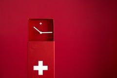 Horloge suisse rouge sur le fond rouge Image libre de droits