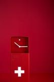 Horloge suisse verticale sur le fond rouge Photographie stock libre de droits