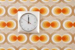 Horloge sur le rétro papier peint Photographie stock libre de droits