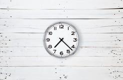 Horloge sur une planche blanche Photos stock