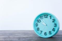 Horloge verte sur une table en bois sur un fond blanc Photographie stock libre de droits