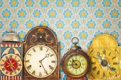 Horloges colorées de vintage devant le rétro papier peint Images libres de droits
