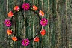 Horloges met bloemen rond op groene houten lijst met plaats voor tekst Stock Fotografie