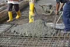 Hormigón colado de los trabajadores de construcción usando la manguera concreta foto de archivo
