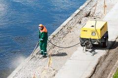 Hormigón de limpieza del trabajador de construcción Foto de archivo libre de regalías