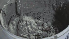 Hormigón de mezcla del primer en cubo vía el taladro eléctrico en el emplazamiento de la obra metrajes