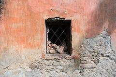 Hormigón y pared de ladrillo quebrados con una ventana con la reja del hierro fotos de archivo