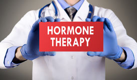 Hormone therapy. Doctor`s hands in blue gloves shows the word hormone therapy. Medical concept Royalty Free Stock Photos