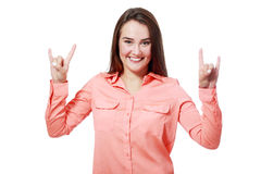 Horn gesture. Young girl doing horn gesture over white background Stock Photo