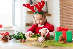 Horn på kronhjort för ren för gullig för förskolebarnflicka som iklädd dräkt för ren bärande gör julkransen i vardagsrum arkivfoton