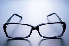 Horn-rimmed glasses on blue background. Horn-rimmed glasses with reflection on blue background Stock Photos
