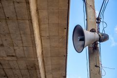 Horn speaker on electrical pol with cement bridge and blue sky background stock photo