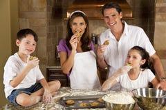 Hornada de la familia y galletas de la consumición en una cocina Foto de archivo libre de regalías